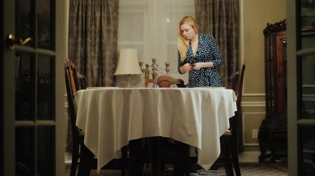 dobras : A young woman sets the table for dinner. Folds out cutlery - knives and forks Vídeos