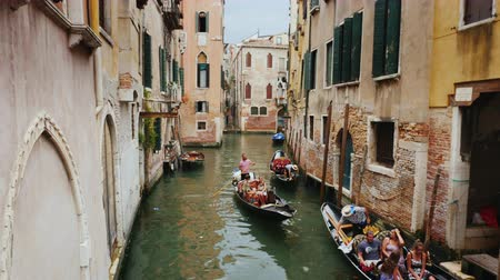 water taxi : Venice, Italy, June 2017: Several gondolas with tourists swim in a narrow canal in the center of Venice. The traditional architecture of Venice Stock Footage