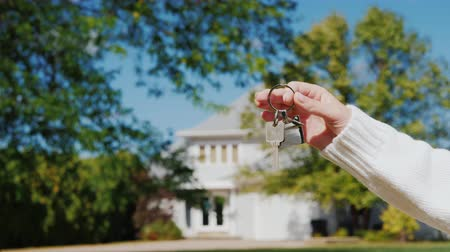 trousseau de clés : A hand with a keychain in the shape of a small house and keys. Against the background of a typical house in the American suburban style