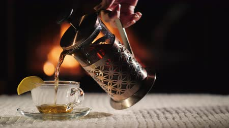 obrus : Pour tea into a cup on the background of the fireplace. Tea in a cozy setting