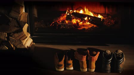 firebox : Top view of A few pairs of winter shoes are drying near the fireplace where the fire is on.