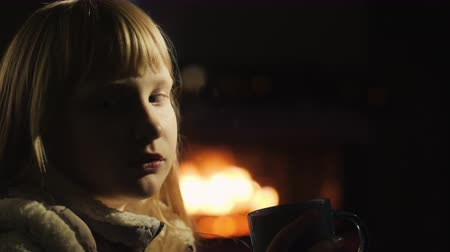 сохранять : Girl drinks tea sitting by the window, a fireplace and a Christmas tree are lit from behind