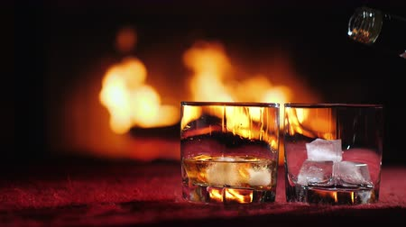 viski : Whiskey is poured into a glass with ice on the background of the fireplace Stok Video