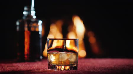 viski : Glass with strong alcohol and a bottle on the background of the fireplace Stok Video