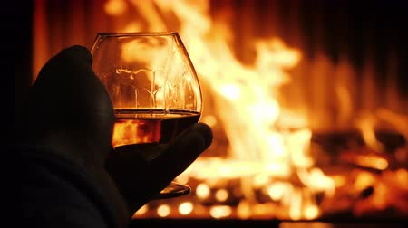 cognac : Male hand with a glass of cognac on the background of the fireplace, tasting in a cozy setting