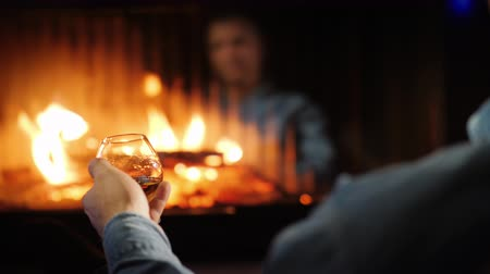sterke drank : A man drinks brandy by the fireplace, his face is reflected in the glass of the furnace Stockvideo