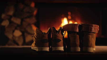 firebox : Two pairs of winter shoes are drying near the fireplace. Romantic winter evening Stock Footage