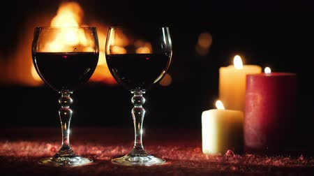 şömine : Two glasses with red wine against the background of the fireplace where the fire is burning