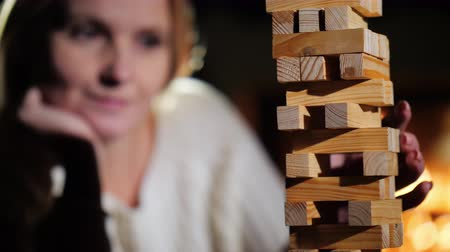 preciso : Portrait of a woman playing a board game where you need to pull out wooden blocks from the tower Vídeos