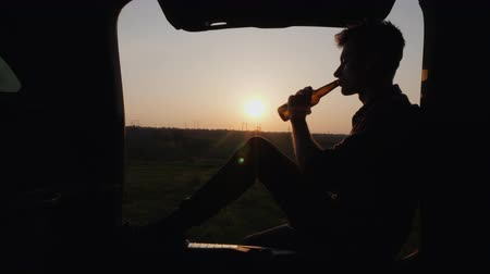 hayran olmak : A teenager sits in the trunk of a car and drinks beer from a bottle
