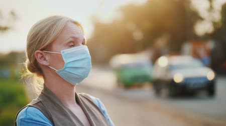respirator : Dirty air - a woman in a gauze bandage stands near a road loaded with vehicles Stock Footage
