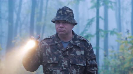 ориентация : A man in camouflage is walking through the forest with a flashlight in his hand. Wet rainy weather in the early morning Стоковые видеозаписи