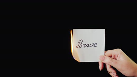 sentiment : Man burns a paper with the inscription Brave