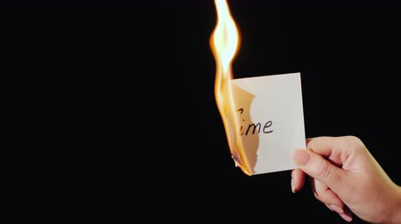 sentiment : Man burns a paper with the inscription Time Stock Footage