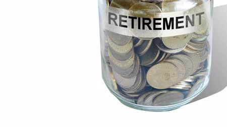 retirement : money into retirement fund jar isolated against white