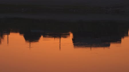 tragédia : Small houses are reflected on the surface of the river early in the morning. The surface of the river from the red dawn