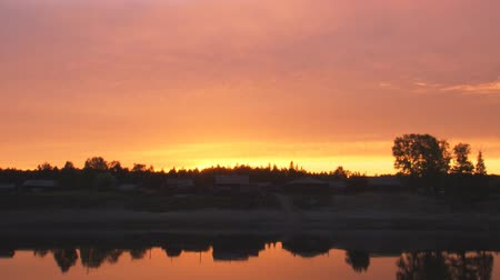 tragédia : Dawn over the village. Village on the banks of the river. In the river reflected the red sky and the village