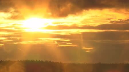 ışınları : The sun sets over the forest behind the clouds. Time lapse. Summer evening
