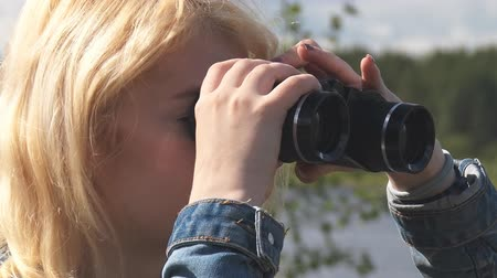 vöröshajú : A teenage girl looking through binoculars, then lowers it. Face shot close up Stock mozgókép