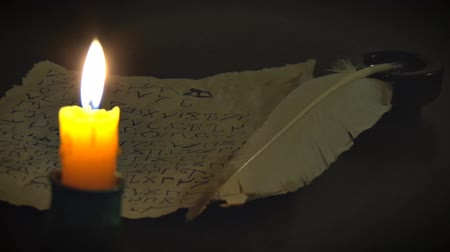 poezja : Ancient Manuscript and Burning Candle. The manuscript was written with a quill pen in an unknown alphabet. Next to the candle holder lit candle.
