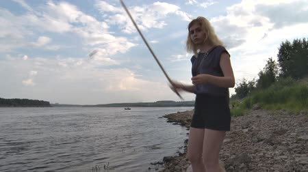voluntário : Girl Catches Fish with Bait. Girl skewer the bait on the hook and throws the bait into the river. Blonde catches a fish