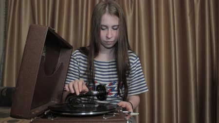 gramophone : Girl Listens to Phonograph. Girl turns the handle of the gramophone and listening to music from gramophone records