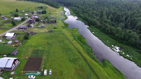 Flight over Village and River. Flying over the village and the river forest shores in the summer. In the village there are wooden houses and tourist tents