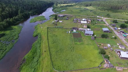 Drone flies over Village and River. Flying over the village and the river forest shores in the summer. In the village there are wooden houses and tourist tents Stock Footage