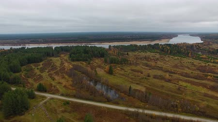 Flight over Field and Road. Drone flying over forest, field, bog and lake. Far ahead you can see the river. The Northern nature in the fall. Among the swamps the road, the road car rides