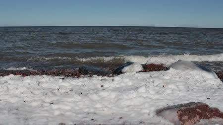 Sea Shore in Winter. Sea waves hit the rocks on the shore in the winter. On the banks of snow. The weather is Sunny.