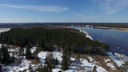Forest and River in Spring Time. Video from the quadcopter over the forest and the river in the spring. The river is still floating ice. On the ground the snow