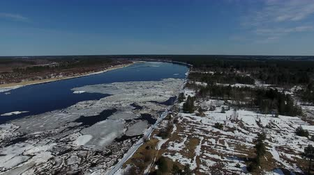 Ice On River In Spring Top View. Video from the quadcopter over the forest and the river in the spring. The river is still floating ice. On the ground the snow