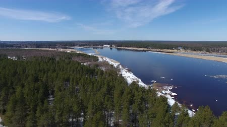 Flying Over Forest And River In Spring. Video from the quadcopter over the forest and the river in the spring. The river is still floating ice. On the ground the snow