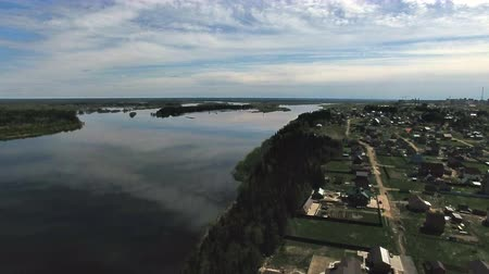 Small town on Banks of a Large River. The video is taken from the copter flying over the small town, located on the banks of the big river in the spring.
