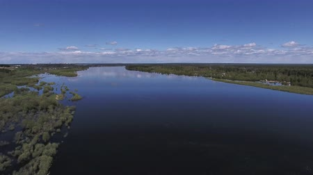 Rise above River in Spring. The video is taken from the copter, flying over a large river in the spring during the flood. The trees have recently appeared on fresh leaves. The shore with shrubs flooded