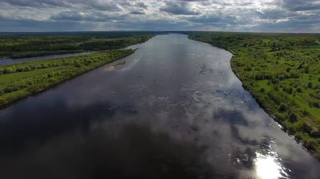Flying over Big River in Summer. Video shoot with the copter flying over the wide river during the early summer. The water reflects the sky. On the banks of the river grows forest