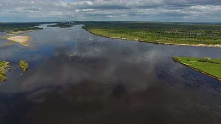 Flying over Great Northern River. Video shoot with the copter flying over the wide river during the early summer. The water reflects the sky. On the banks of the river grows forest Stock Footage