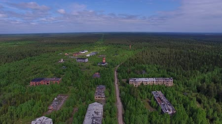 Dead Town in Wild Forest. The video is taken from a quadrocopter over a dead forest. Brick houses dilapidated, the Windows had no glass, the roof is broken. The view is similar to post-apocalyptic Stock Footage