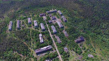 Dilapidated Houses of the Dead Town in Forest. The video is taken from a quadrocopter over a dead forest. Brick houses dilapidated, the Windows had no glass, the roof is broken. The view is similar to post-apocalyptic