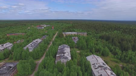 Flying over Dead Town in Forest. The video is taken from a quadrocopter over a dead forest. Brick houses dilapidated, the Windows had no glass, the roof is broken. The view is similar to post-apocalyptic