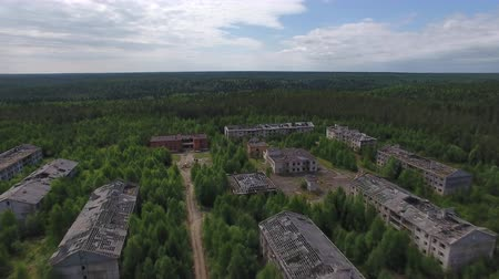 Dead Town in Forest. The video is taken from a quadrocopter over a dead forest. Brick houses dilapidated, the Windows had no glass, the roof is broken. The view is similar to post-apocalyptic