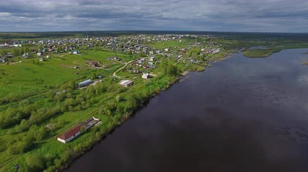 Flying over River to Town. The video is taken from a quadrocopter flying over a large Northern river. On the river Bank there is a small town. Further out of town there is a forest to the horizon