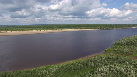 Camera Flies over North River in Summer. Quadrocopter with a camera flying over the shore to the big river. On the river you can see a small boat Stock Footage