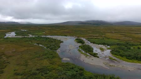 Flying over Tundra in Autumn. The drone from which the video is shot, flies over the tundra to the mountains. A small river flow through the tundra