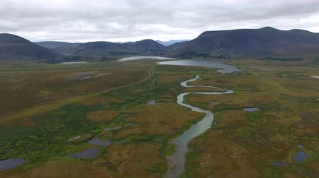 Flying over River in Tundra to Mountains. The drone from which the video is shot, flies over the tundra to the mountains. A small river flow through the tundra