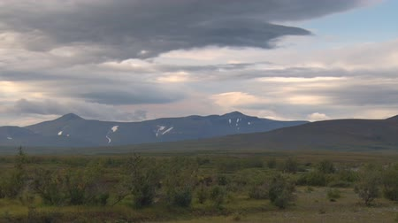 arctic tundra : Clouds Move Quickly over Mountain. They are flying clouds. In the tundra grows small bushes Stock Footage