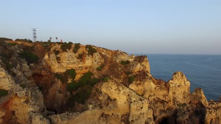 ponta da piedade : Ponta da Piedade lighthouse on cliff near ocean at sunset, Lagos, aerial view Stock Footage