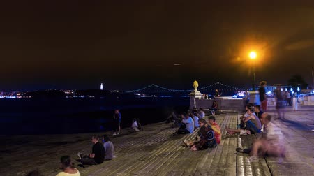 comercio : People rest at night on the waterfront of the River Tagus, Lisbon, timelapse