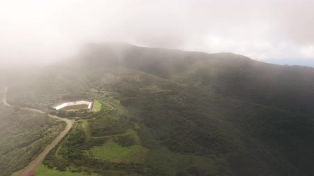 еще : Flying in clouds over mountains and forest of Madeira, Portugal aerial view