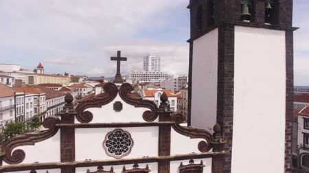 sao miguel : Saint Sabastian church with clock tower in Ponta Delgada on Sao Miguel Island in Azores, Portugal. Beautiful church in early morning under white clouds. Stock Footage